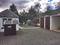 rear gravelled yard with garage and storage sheds